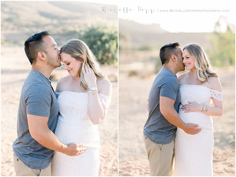dad kissing mom to be on forehead in maternity photo