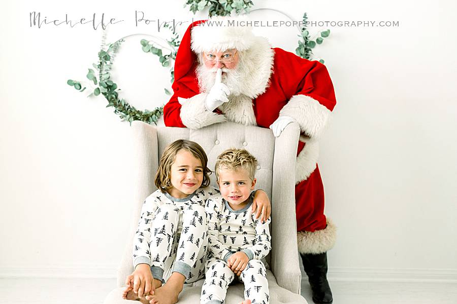 brothers sitting on chair with Santa sneaking up behind them
