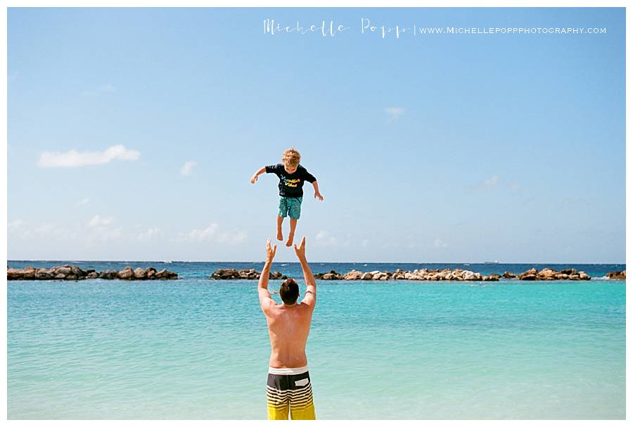 dad throwing son into air at beach