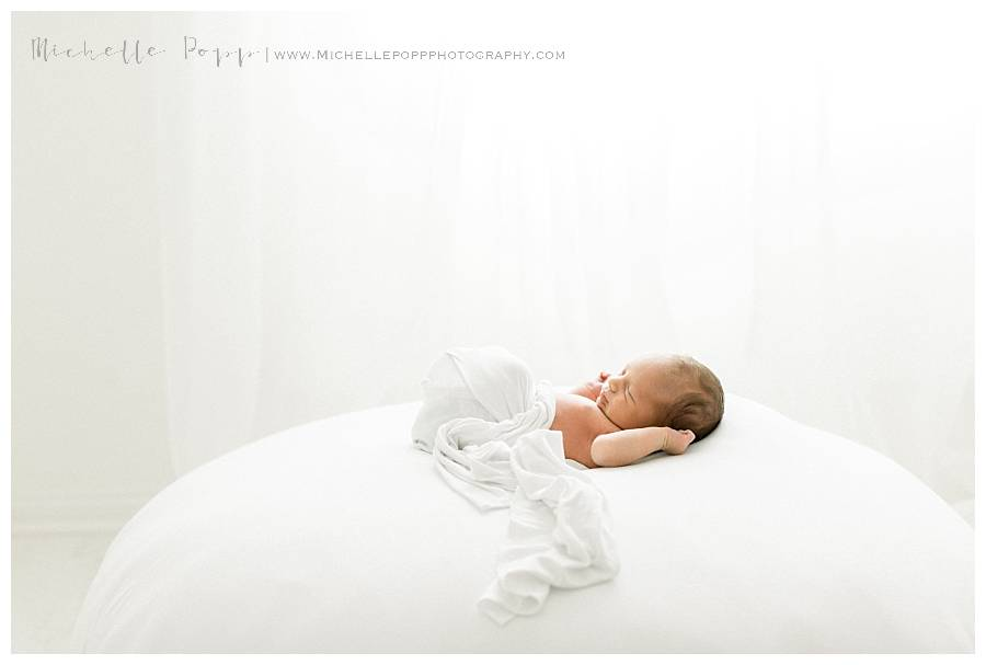 newborn baby on bed in white swaddle