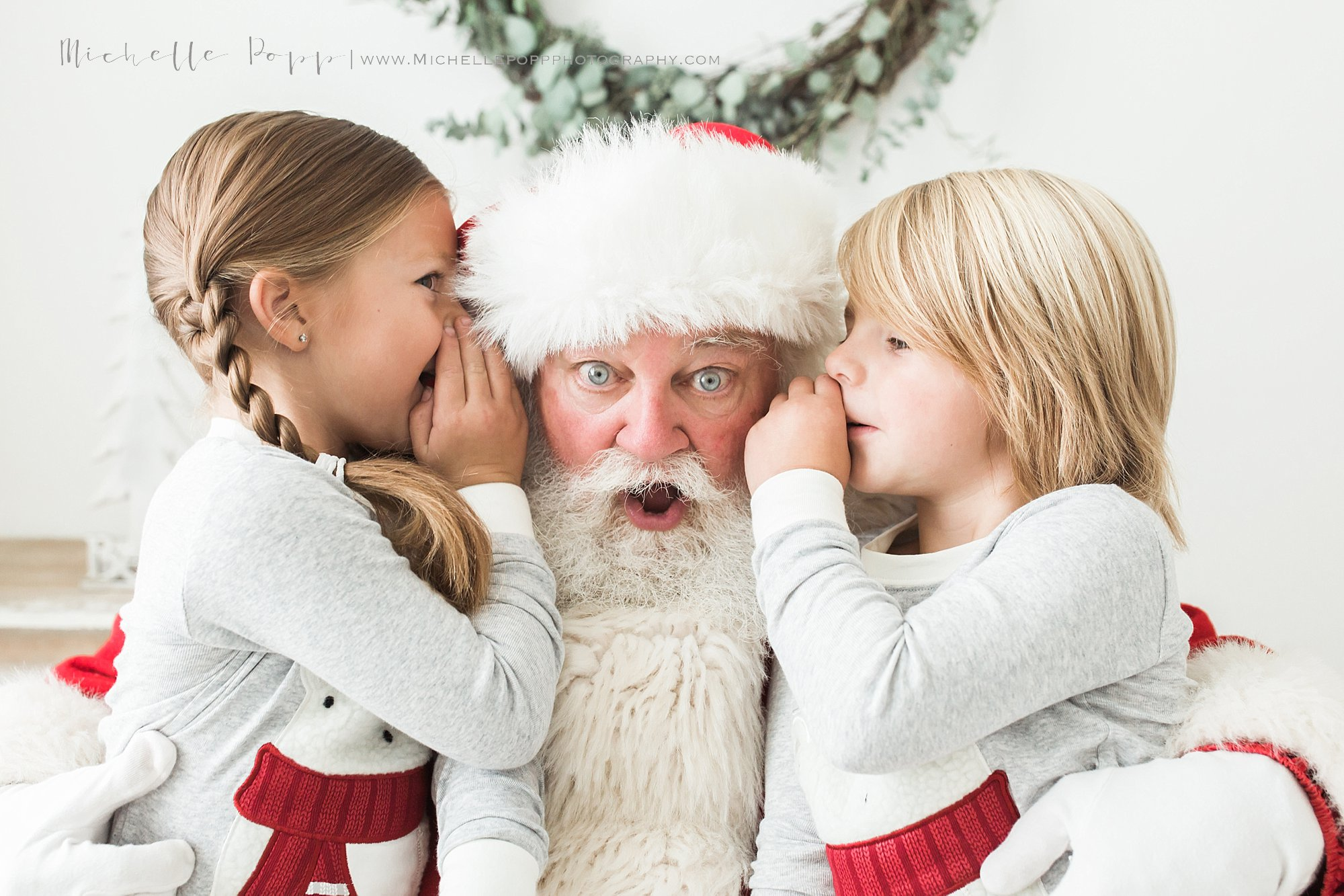 boy & girl whispering into Santa's ear