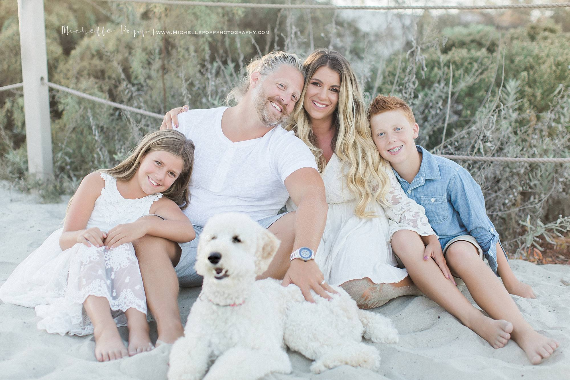 San Diego family beach photography family and dog sitting in the sand smiling