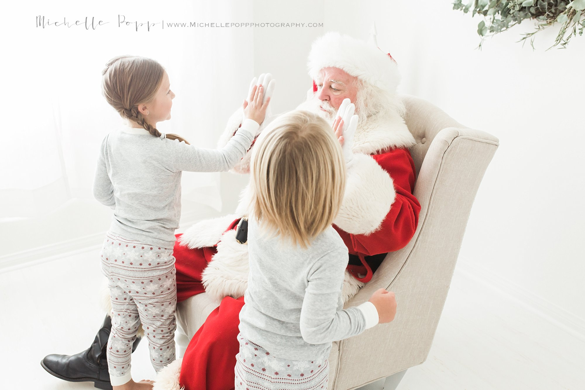 two kids high giving Santa