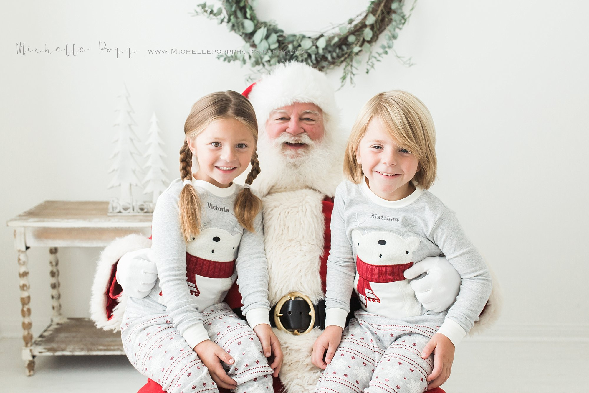 brother sister smiling on Santa's lap