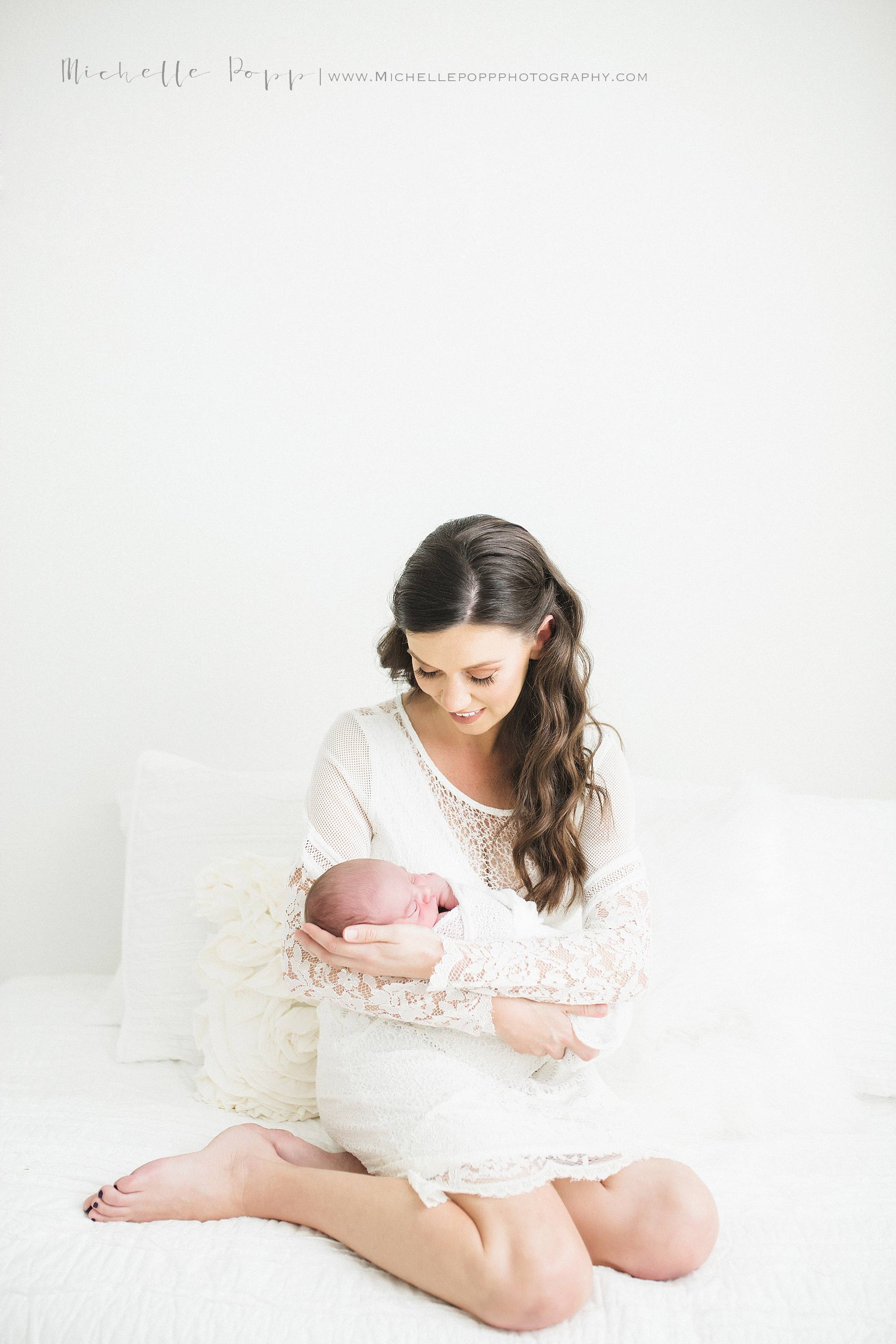 Mom in all white lace dress holding newborn baby
