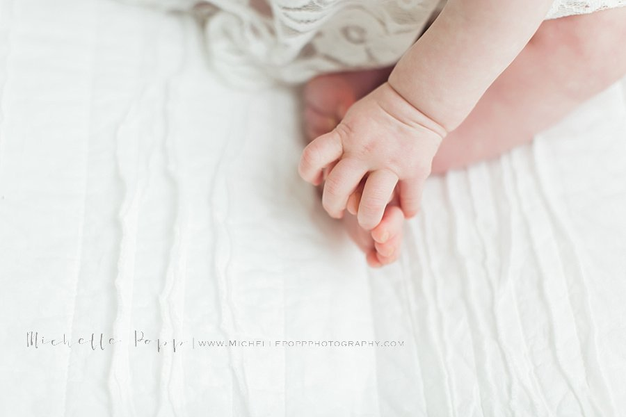 Close up of babys hand grasping toes